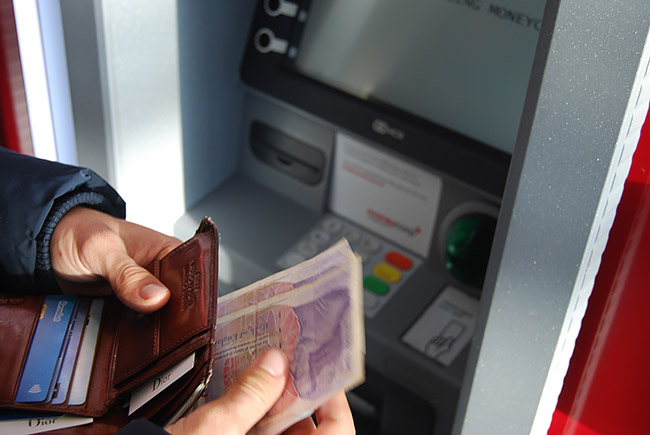 Person withdrawing money from an ATM
