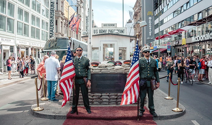 Men standing in faux uniform at Checkpoint Charlie in Berlin
