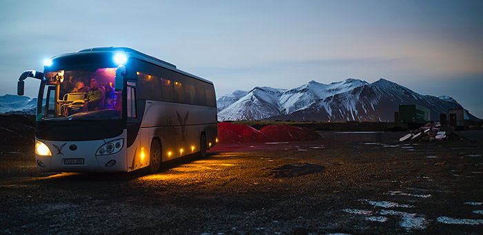 Tour bus parked at sunset outside in Iceland