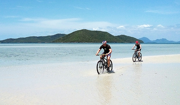 2 people biking on hard sand at Ko Samui, Thailand