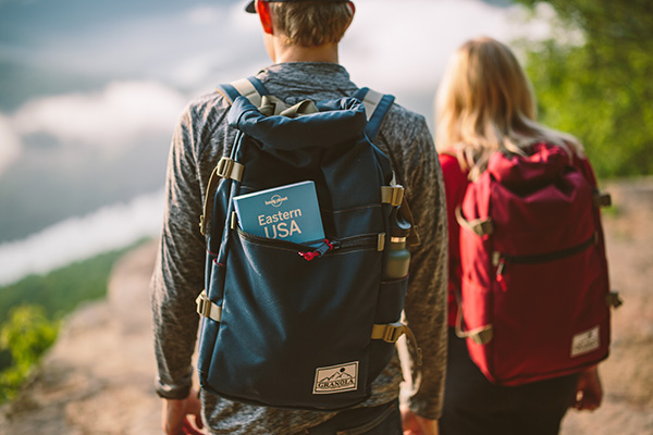 Two young people hiking with backpacks on a trail