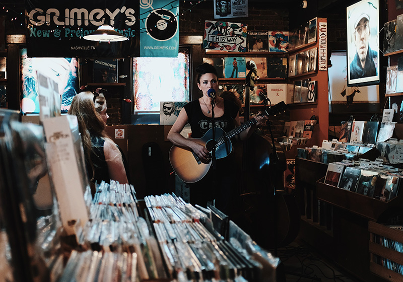 Woman playing guitar in Nashville record store