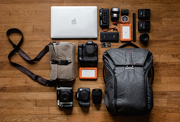 Backpack with photography gear laid out on floor