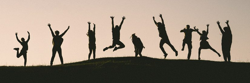 Silhouttes of multiple people making poses on a hill