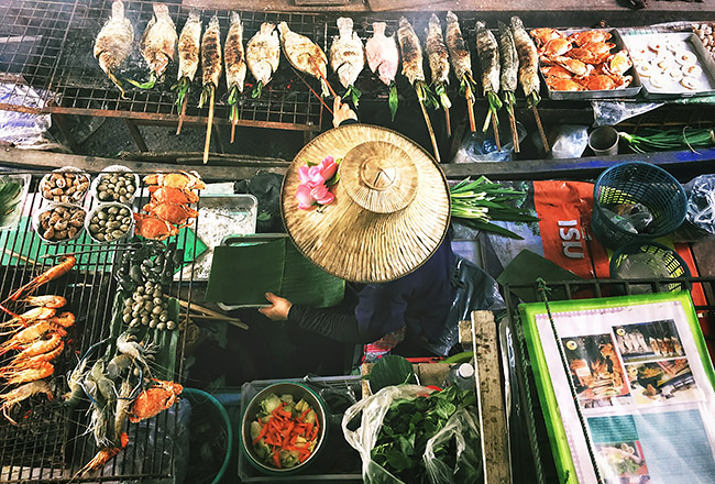 Top down shot of a woman in bangkok preparing street food